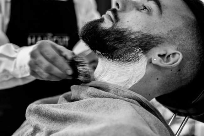 man trimming beard at barber